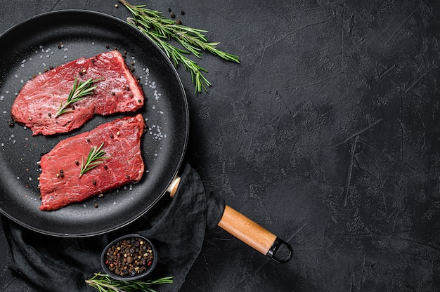 Raw sirloin steak in a frying pan. beef meat. top view. copyspace background