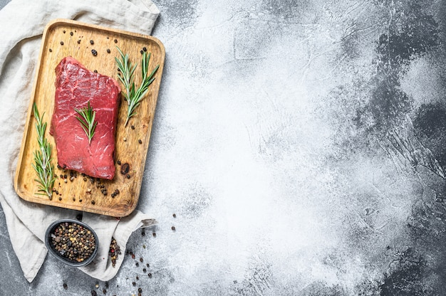 Raw sirloin steak on a wooden tray. beef meat. gray background. top view. space for text