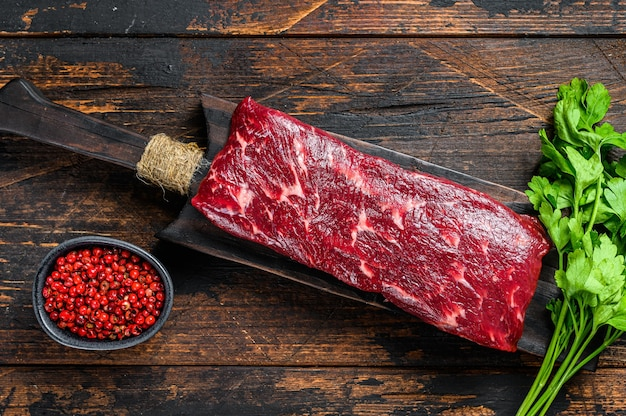 Raw skirt or machete beef meat steak on a cutting board. dark wooden table. top view.
