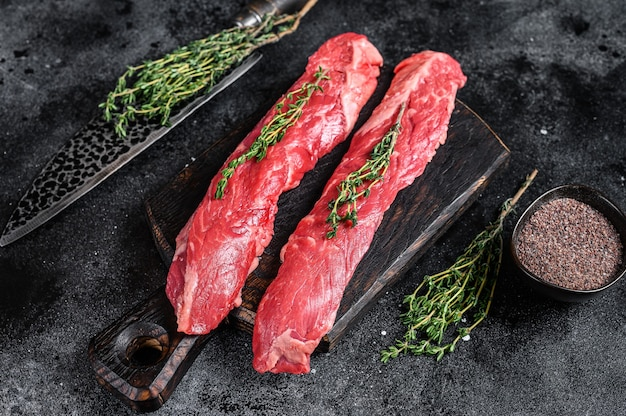 Raw skirt machete beef meat steak on a cutting board with knife