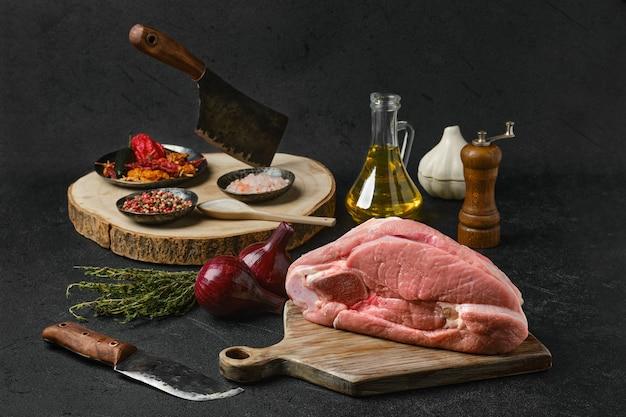 Сырой кусок говядины на пару с кулинарными ингредиентами на черном фоне