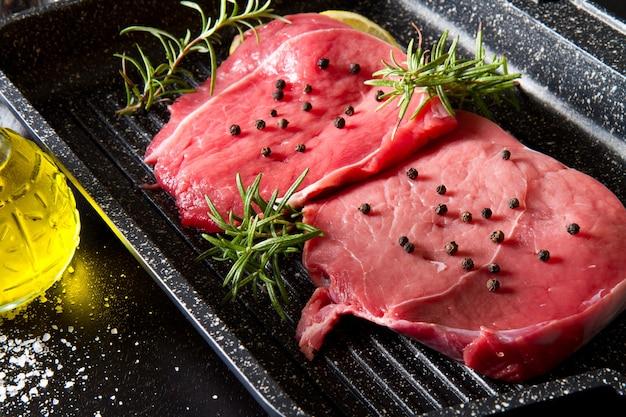 검은 배경에 접시 냄비에 원시 슬라이스 쇠고기