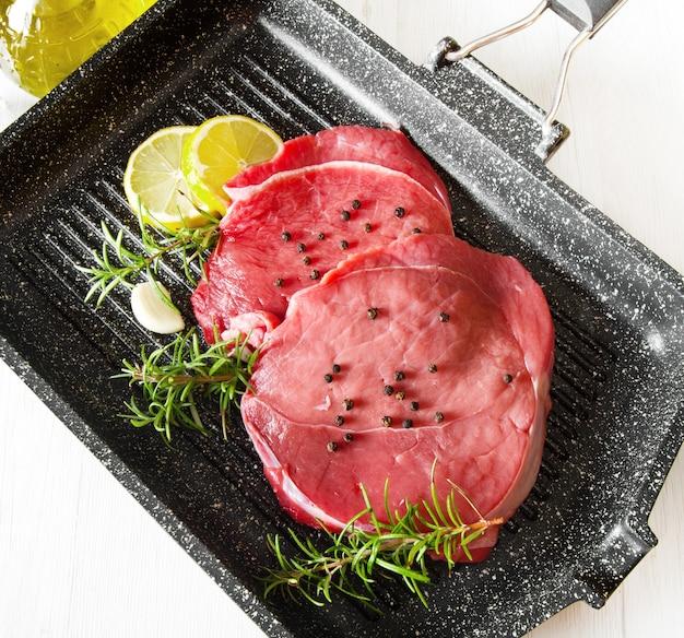 흰색 배경에 접시 냄비에 원시 슬라이스 쇠고기