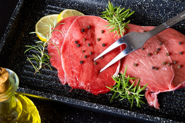 Raw sliced beef on plate pot on black background