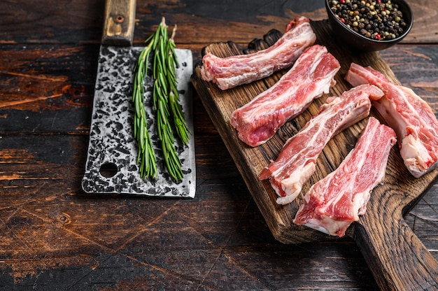 Raw sliced veal short spare loin ribs on a wooden cutting board