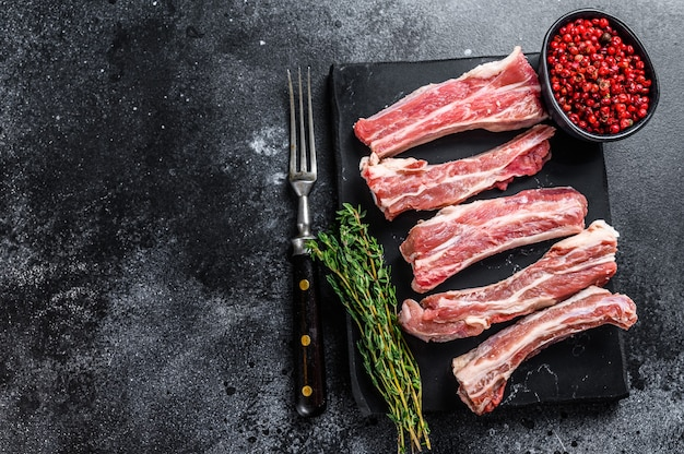 Raw sliced veal spare loin ribs on a marble board