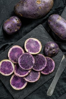 Raw sliced violet potatoes. black background. top view