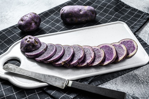 Raw sliced violet potatoes on a white chopping board. gray background. top view