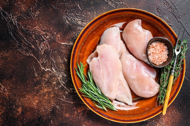 Сырые кусочки стейков из филе куриной грудки на деревенской тарелке с зеленью. темный фон. вид сверху. скопируйте пространство.