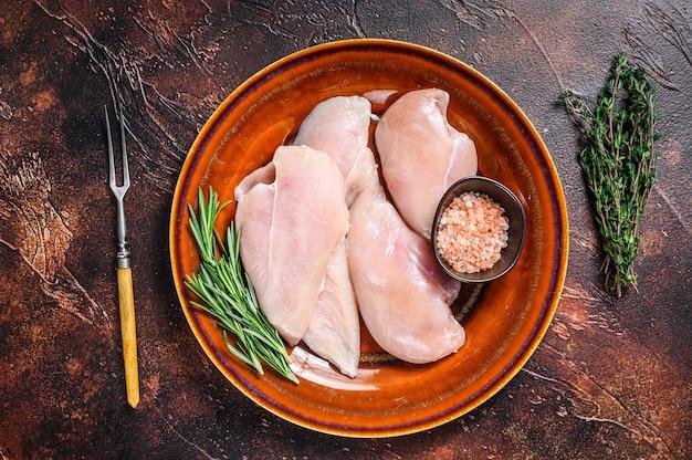 Сырые кусочки стейков из филе куриной грудки на деревенской тарелке с зеленью. темный фон. вид сверху.