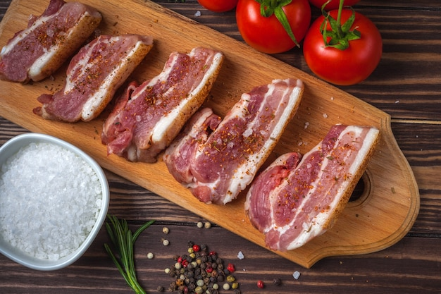 Raw slices of pork bacon on a cutting board, on a rural wooden tabletop. pork belly