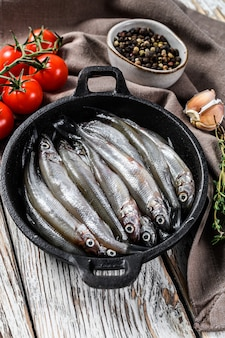Raw smelt with pepper and thyme in a pan