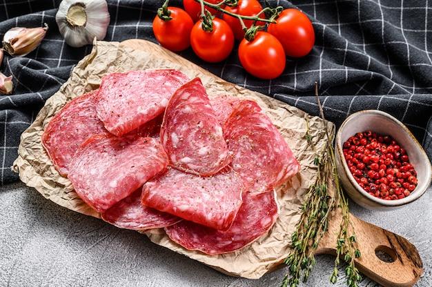 Raw smoked salami sausage slices. gray background.