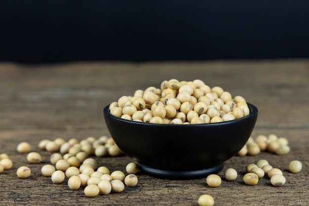 Raw soybeans in wooden bowl on wooden table background.