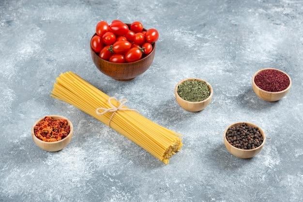 Сырые спагетти, миска с помидорами и специями на мраморном фоне.