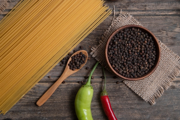 Raw spaghetti and bowl of peppercorns placed on wooden surface. high quality photo