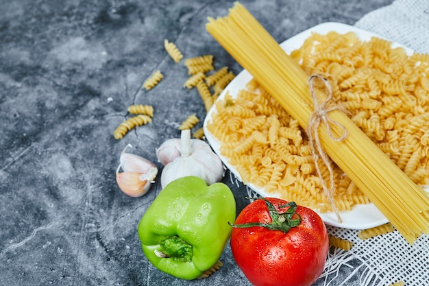 Raw spaghetti and fusilli on a white plate with tomato, pepper, and garlic.