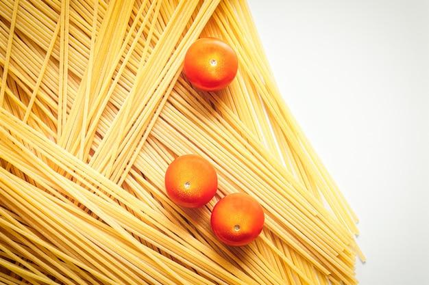 生のスパゲッティイタリアンパスタは未調理で、トマトはレストランで調理する準備ができています。イタリア料理とメニューのコンセプト