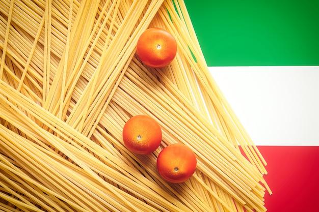 生のスパゲッティイタリアンパスタは未調理で、トマトにはイタリア国旗が付いています。イタリア料理とメニューのコンセプト