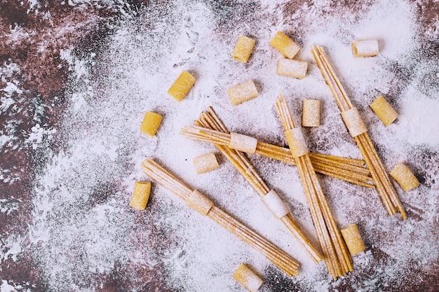 Spaghetti crudi e maccheroni sulla tavola di legno farinosa.