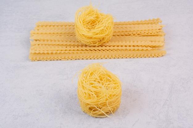 Nido di spaghetti crudi e pasta lunga sulla superficie della pietra