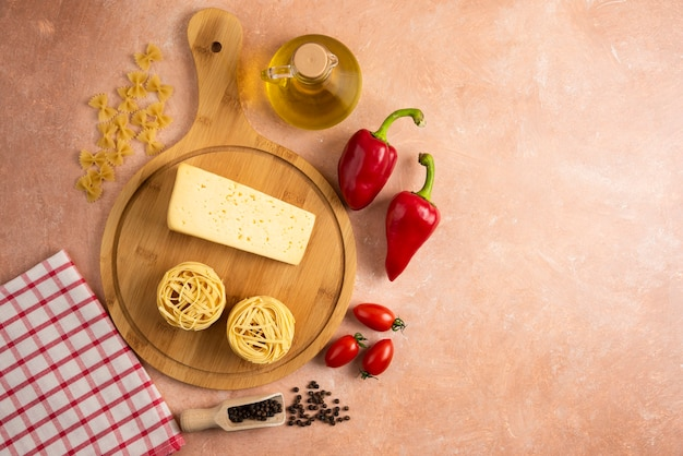 Сырые гнезда спагетти и сыр на деревянной доске с овощами.