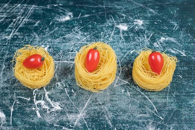 원시 스파게티 둥지와 파란색 배경에 토마토입니다. 고품질 사진