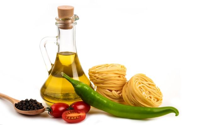 Сырые гнезда спагетти, свежие овощи и бутылка масла на белом.