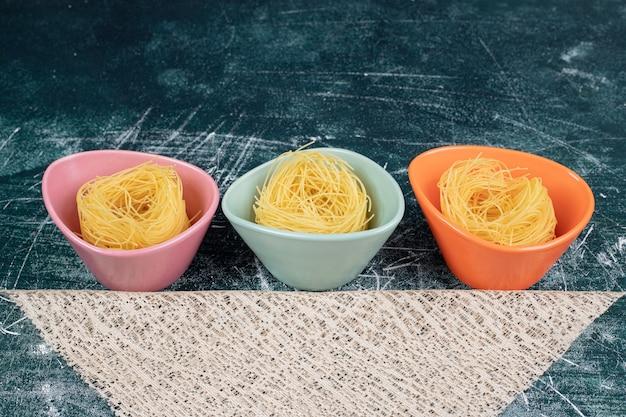 カラフルなボウルと黄麻布に生のスパゲッティが巣を作ります。高品質の写真