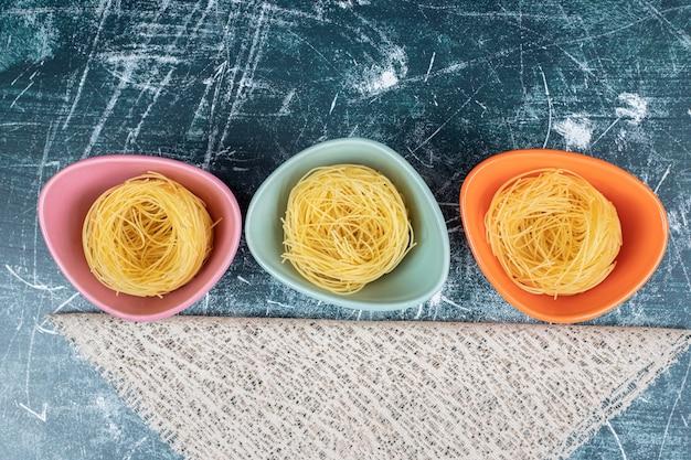 다채로운 그릇과 삼 베에 원시 스파게티 둥지. 고품질 사진