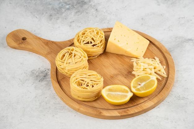 生のスパゲッティの巣、レモンチーズの木の板。