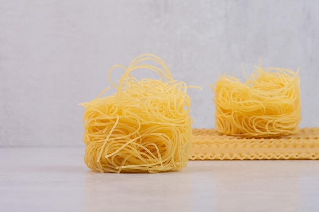 Raw spaghetti nests and pasta on marble table.
