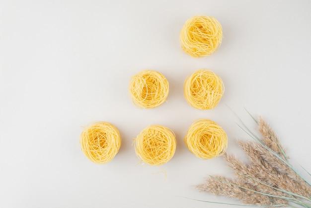 Nidi di spaghetti crudi su superficie bianca con grano