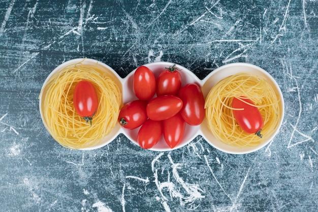 파란색 배경에 토마토와 원시 스파게티 둥지. 고품질 사진