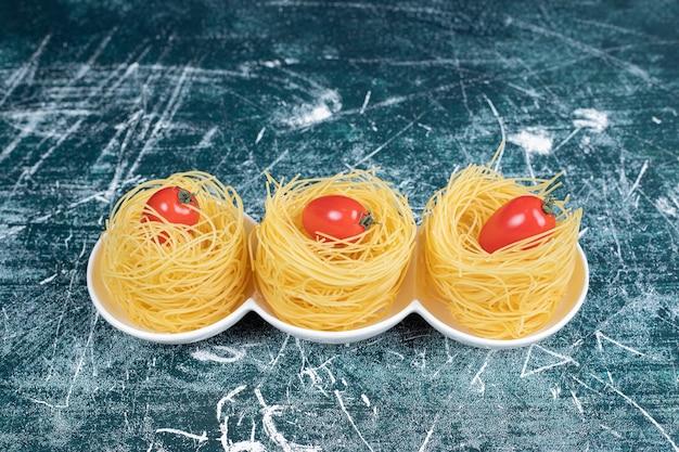 하얀 접시에 토마토와 원시 스파게티 둥지. 고품질 사진