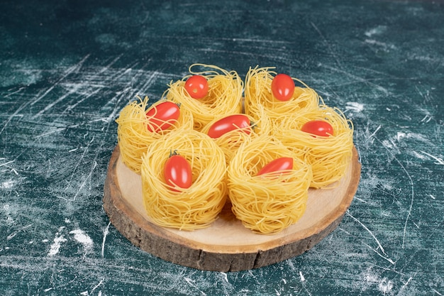 나무 보드에 토마토와 원시 스파게티 둥지. 고품질 사진