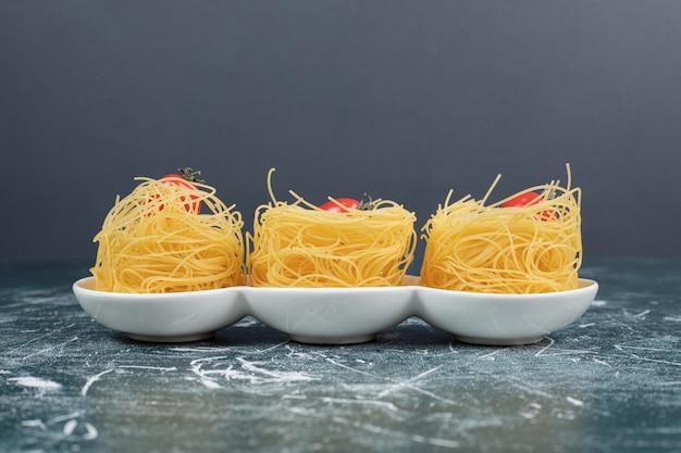 Nidi di spaghetti crudi con pomodori sul piatto bianco. foto di alta qualità