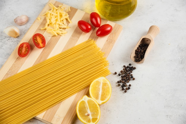 Raw spaghetti, oil and fresh vegetables on wooden board.