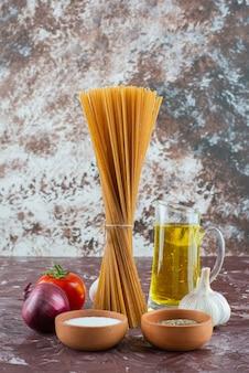 大理石の表面に生のスパゲッティ、オリーブオイル、新鮮な野菜。