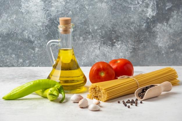 白いテーブルの上に生のスパゲッティパスタ、オリーブオイルのボトル、コショウの粒と野菜。