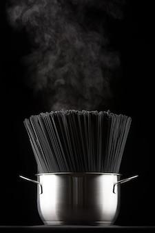 Сырые макароны спагетти на черном в кастрюле, идет пар