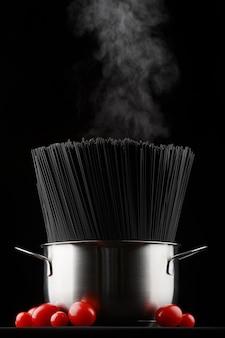 Сырые макароны спагетти на черном в кастрюле со свежими помидорами, идет пар