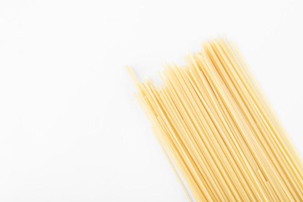 Pasta cruda degli spaghetti su bianco.