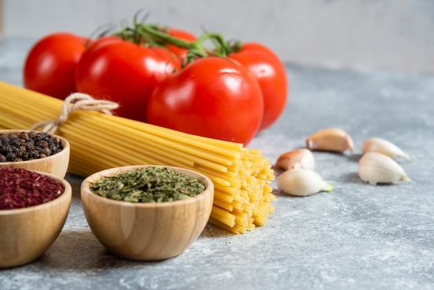 Сырые спагетти, специи и помидоры на мраморном фоне.