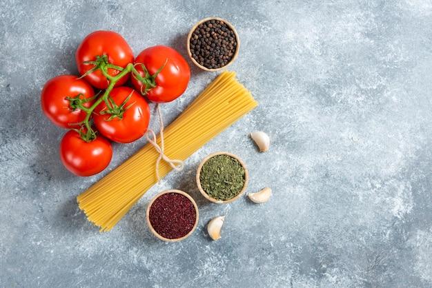 원시 스파게티, 향신료와 토마토 대리석 배경.