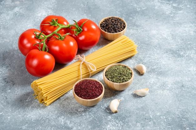 大理石の背景に生のスパゲッティ、スパイス、トマト。