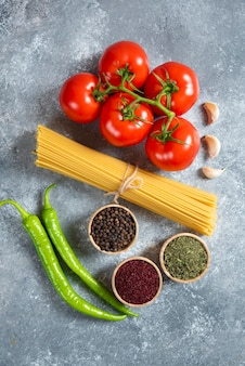 Spaghetti crudi, spezie e pomodori su fondo di marmo.