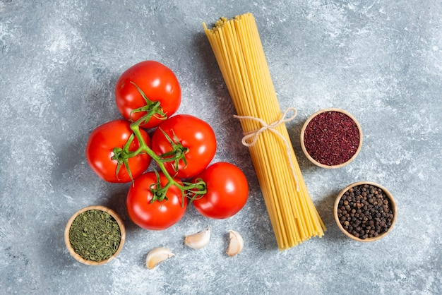 Raw spaghetti, spices and tomatoes on marble background.