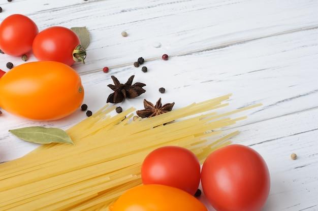 白い木製のテーブルに生のスパゲッティ、トマト、スパイス。