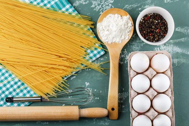 Spaghetti crudi con uova, mattarello, frusta, grani di pepe e amido